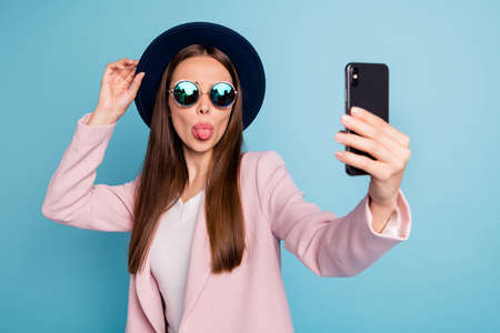 Portrait of playful carefree girl using her cell phone making self photo blogging showing her tongue fooling wearing pink topcoat isolated over blue background Stock Photo