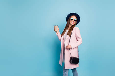Portrait of lovely sweet girl in eyewear eyeglasses walk have stroll with her friends hold mug wear pink top coat denim jeans isolated over blue color background