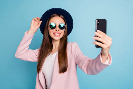 Portrait of charming content candid lady using her cell phone taking selfie having stroll wearing pink topcoat isolated over blue color background Stock Photo