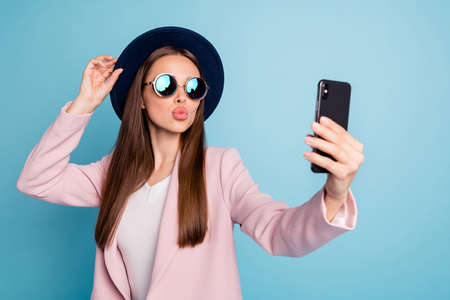 Portrait of dreamy cute girl using her mobile phone making selfie sending air kisses launching blog stream wearing pink stylish topcoat isolated over blue background Фото со стока - 129823326