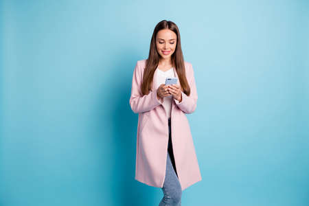 Portrait of cute concentrated lady using her cellphone reading news information wearing topcoat isolated over blue background
