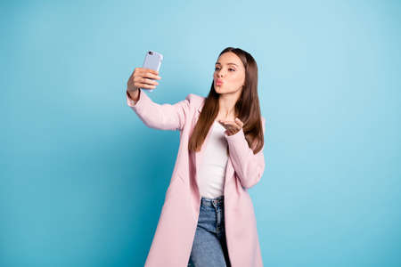 Portrait of cute charming lady sending air kisses to her boyfriend taking selfie wearing topcoat denim jeans isolated over blue color background Stock Photo