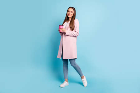 Full length photo of lovely dreamy girl having rest break holding take-out enjoy walk wearing topcoat denim jeans isolated over blue color background Stok Fotoğraf