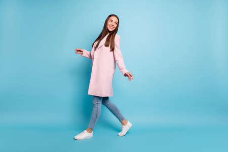 Full body profile photo of amazing lady in good mood going shopping wear demi-season coat and jeans isolated blue background