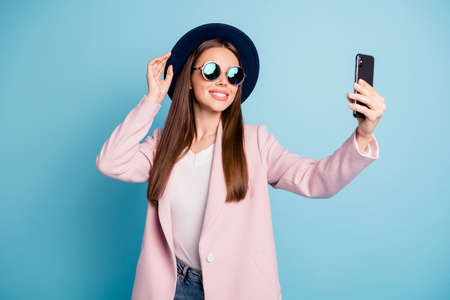 Portrit of sweet lovely girl using her cell phone making selfie posing touching her fashionable hat wearing pink topcoat isolated over blue background Stock Photo