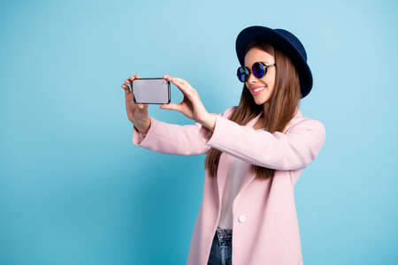 Profile side photo of cheerful girl using her cell phone making self portrait enjoying promenade wearing pink outfit isolated over blue background