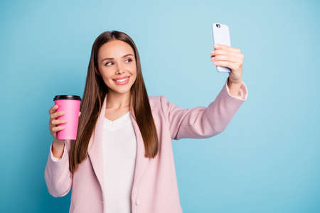Portrait of cute cheerful lady using her cellphone making selfie holding mug with hot beverage wearing pink coat isolated over blue color background 스톡 콘텐츠 - 129823341