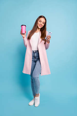 Full size photo of cute lovely girl using her cell phone reading news wearing denim jeans topcoat isolated over blue background