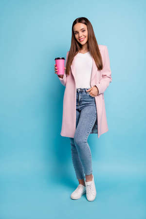Full length photo of charming cheerful glad lady in topcoat having stroll rest holding mug wearing denim jeans isolated over blue color background