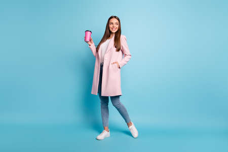 Full size photo of lovely cute cheerful girl having walk promenade holding mug wearing coat denim jeans isolated over blue background Stok Fotoğraf