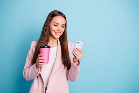 Portrait of charming cheerful lady using her cell phone reading news blogs wearing topcoat isolated over blue color background