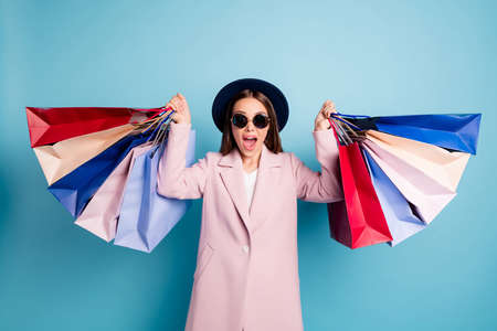 Portrait of astonished funny lady in eyewear eyeglasses go shopping find wonderful bargain hold bags scream wow omg wear season coat isolated over blue color background