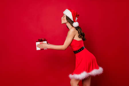 Beautiful lady holding large wrapped giftbox in hands took it to address wear fluffy mini dress isolated red background
