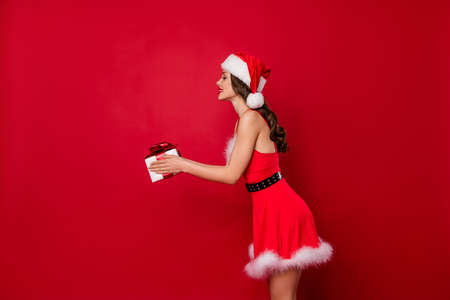 Beautiful lady holding large wrapped giftbox in hands took it to address wear fluffy mini dress isolated red background Banco de Imagens