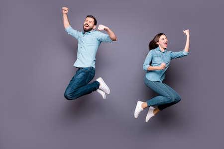 Foto de tamaño completo de estudiantes encantados saltar, levantar los puños, gritar, sí, celebrar la victoria, usar jeans de mezclilla aislados sobre fondo gris