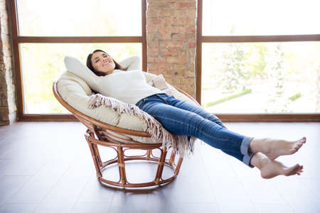 Full length body size view of her she nice attractive charming winsome lovely peaceful dreamy cheerful cheery woman lying on cosy pillow chair stretching in industrial loft brick style interior room