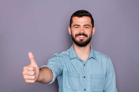 Portrait of cheerful man show his thumb up like advertise adverts wearing denim jeans shirt isolated over grey background
