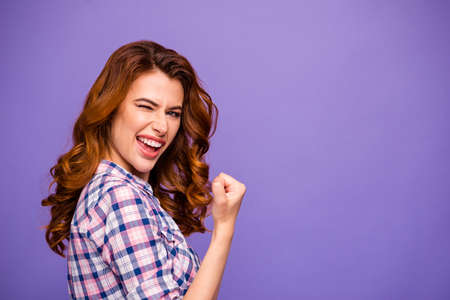 Photo of pretty foxy lady champion winking eye raising fist well done job wear plaid casual shirt isolated purple color background Stock fotó