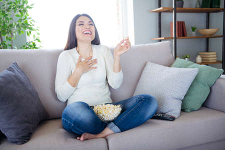 Portrait of her she nice attractive charming lovely cheerful cheery glad positive woman sitting in lotus position on divan watching funny series on TV in light white interior living-room indoors