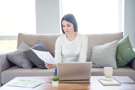 Portrait of her she nice attractive charming smart clever intelligent focused woman holding in hand document making presentation report online research market in light white interior living-room