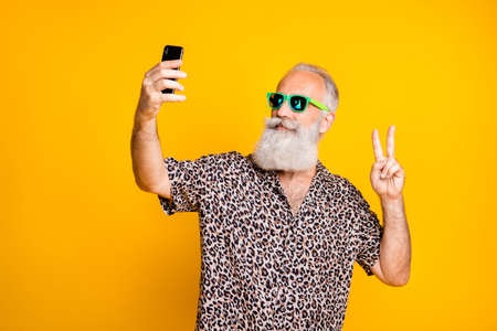 Portrait of positive funny funky old long bearded man on travel summer holidays trip make selfie v-signs wear eyewear eyeglasses isolated over yellow background