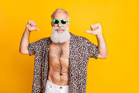 Photo of old man thumbing at himself being proud and advertising himself while isolated with yellow background
