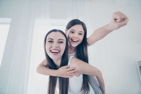 Close-up portrait of two nice beautiful attractive lovely charming cute cheerful cheery excited glad excited people spending free time having fun rejoicing fooling in light white interior room