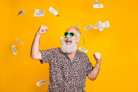 Portrait of crazy retired funky bearded old man with eyeglasses eyewear raise his fists scream yeah celebrate victory look at money falling wearing leopard shirt isolated over yellow background