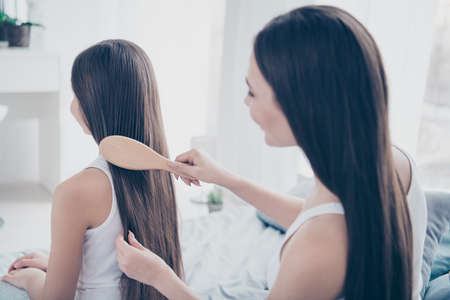 Close-up profile side view portrait of two nice beautiful attractive lovely tender groomed affectionate careful kind people making hair style keratin treatment in light white interior room indoors
