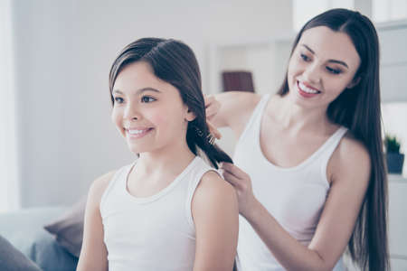 Close-up portrait of two nice beautiful attractive lovely pretty cute tender sweet affectionate cheerful careful kind people making hairstyle hairdress assistance in light white interior room indoors Stock Photo