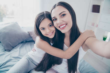 Self-portrait of two nice beautiful attractive lovely charming cute tender sweet affectionate cheerful cheery people bonding embracing spending holiday in light white interior room indoors Banco de Imagens