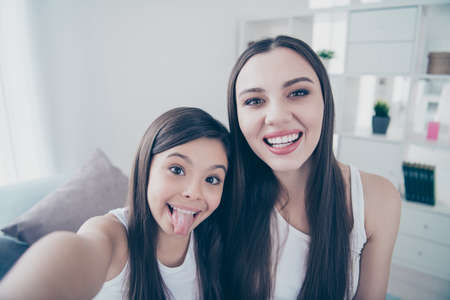 Self-portrait of two nice beautiful attractive cute cheerful comic hilarious foolish girlish long haired people having fun spending free time in light white interior room indoors