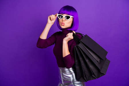 Beautiful stylish lady holding many packs in hands send air kiss dressed in trendy outfit isolated purple background
