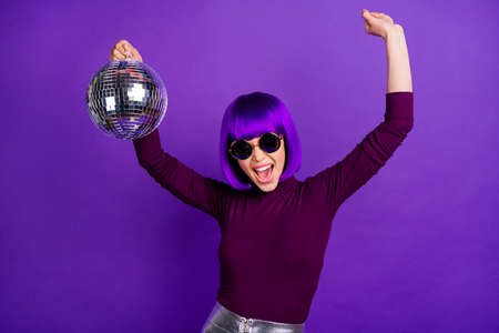 Portrait of cheerful girl with eyeglasses eyewear raising her arms screaming holding glowing ball wearing turtleneck isolated over purple violet background
