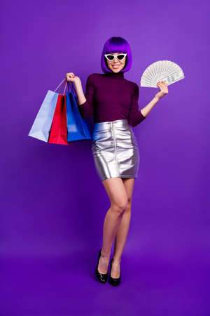 Vertical full body photo of stylish lady holding packs and fan of bucks wear trendy outfit isolated purple background