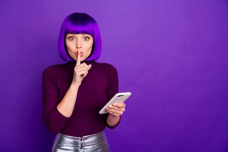 Pretty lady with telephone ask people keep silence and listen news wear trendy clothes and wig isolated purple background