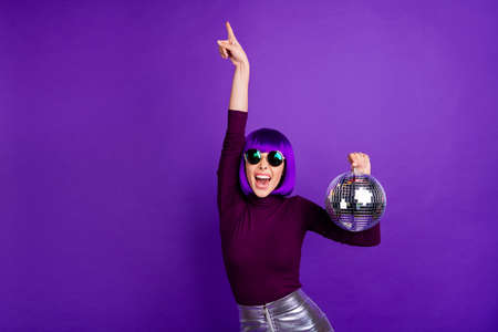 Portrait of cheerful girl with eyewear eyeglasses raising hands wearing turtleneck silver skirt isolated over purple violet background 스톡 콘텐츠