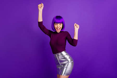 Portrait of cheerful lady raising her fists screaming yeah wearing turtleneck isolated over purple violet background
