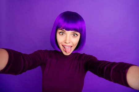 Pretty lady making self photos sticking tongue out mouth wear trendy clothes and wig isolated purple background