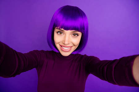 Pretty lady making self photos wear trendy clothes and wig isolated purple background