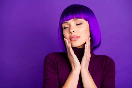 Close up photo of charming girl with her eyes closed touching cheeks wearing turtleneck isolated over violet purple background