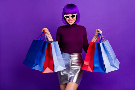 Amazing stylish lady holding packs in hands wear sun specs trendy outfit isolated purple background 스톡 콘텐츠