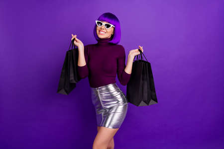 Amazing stylish lady holding many packs in hands wear sun specs trendy outfit isolated purple background