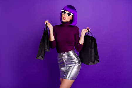 Beautiful stylish lady holding many packs in hands send air kiss wear trendy outfit isolated purple background