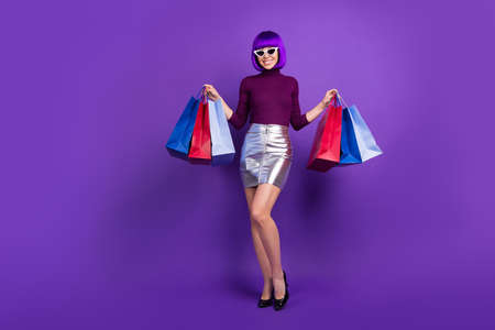 Full length photo of stylish lady holding packs in hands wear trendy outfit isolated purple background 스톡 콘텐츠