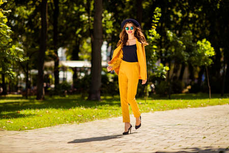 Full length body size view of her she nice-looking attractive lovely trendy pretty cheerful wavy-haired girl on high heels spending fall autumn on fresh air in green park outdoors