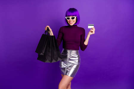 Fashionable lady in wig holding many packs and plastic card in hands dressed in trend outfit isolated purple background