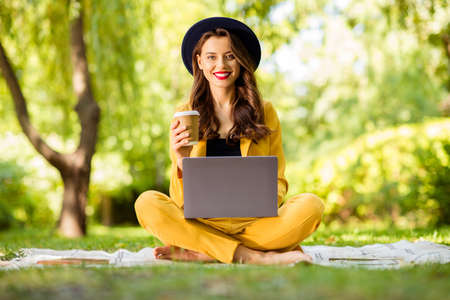 Portrait of her she nice-looking attractive lovely charming trendy pretty cheerful glad wavy-haired girl sitting in lotus pose drinking latte using digital laptop in green park outdoors