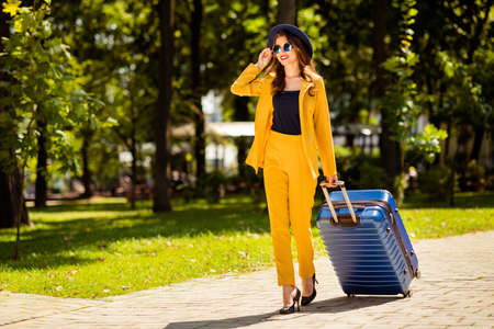 Full length body size view of nice-looking attractive lovely trendy pretty cheerful wavy-haired girl on high heels going to airport railway station departure destination abroad in green park outdoors