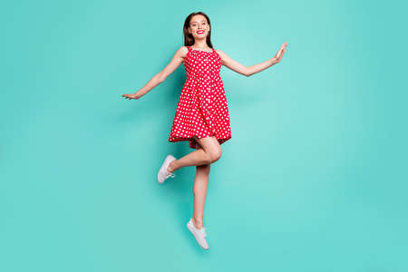 Full size photo of lovely girl smiling jumping wearing polka dot skirt dress isolated over teal turquoise background 스톡 콘텐츠